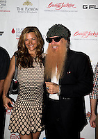 Aug. 29, 2013; Avon, IN, USA: ZZ Top guitarist/vocalist Billy Gibbons (right) on the red carpet with wife Gilligan Stillwater prior to the premiere of Snake & Mongoo$e at the Regal Shiloh Crossing Stadium 18. Mandatory Credit: Mark J. Rebilas-