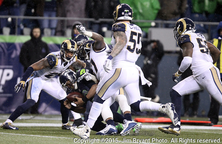 Seattle Seahawks quarterback Russellcfumbles the ball while being tackled by St. Louis Rams defensive end Eugene Sims (97) at CenturyLink Field in Seattle, Washington on December 27, 2015.  The Rams beat the Seahawks 23-17.      ©2015. Jim Bryant Photo. All Rights Reserved