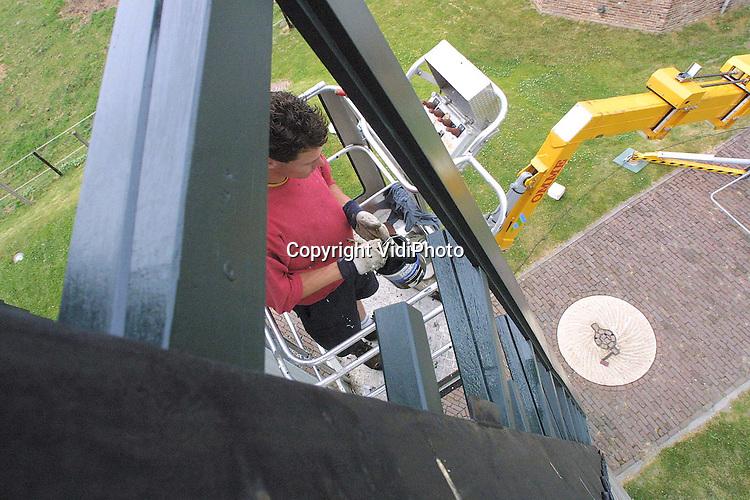 """Foto: VidiPhoto..VALBURG - Personeel van molenmaker Coppes uit Bergharen verft deze week de wieken van de Valburgse standerd windmolen """"Nieuw Leven"""". Tegenwoordig gebeurt dat met een hoogwerker. Behalve dat Nieuw Leven een van de oudste molens van ons land is, dient de molen ook als oefenlocatie voor examenkandidaten van het molenaarsexamen."""