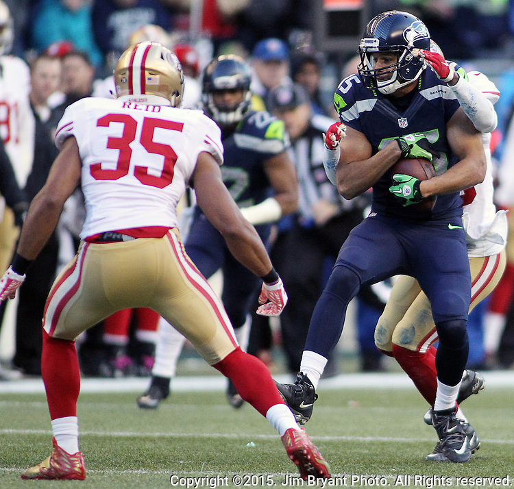 Seattle Seahawks wide receiver Jermaine Kearse (15) protects the ball before getting hit by San Francisco 49ers defensive back Jimmie Ward (25) and safety Eric Reid (35) at CenturyLink Field in Seattle, Washington on November 22, 2015.  The Seahawks beat the 49ers 29-13.   ©2015. Jim Bryant Photo. All RIghts Reserved.