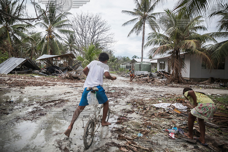 Children on a muddy street on the Nui Atoll, which was badly hit by the Cyclone Pam in March 2015. Lot of debris and sand was deposited on roads which in turn become a quagmire in the rain. The Nui Atoll was affected by storm surges caused by Cyclone Pam in which 12 houses were completely destroyed and 110 homes badly damaged. 71 families (40% of the population) from Nui were displaced and were living in evacuation centres or with other families. According to Tuvalu Prime Minister Enele Sopoaga estimated 45 percent of the nation's nearly 10,000 people were displaced.