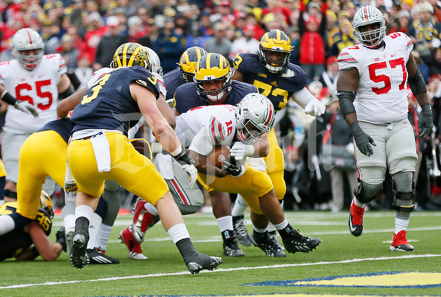 Ohio State Buckeyes quarterback J.T. Barrett (16) scores a touchdown in the first quarter of the college football game between the Michigan Wolverines and the Ohio State Buckeyes at Michigan Stadium in Ann Arbor, Saturday afternoon, November 28, 2015. As of half time the Ohio State Buckeyes led the Michigan Wolverines 14 - 10. (The Columbus Dispatch / Eamon Queeney)