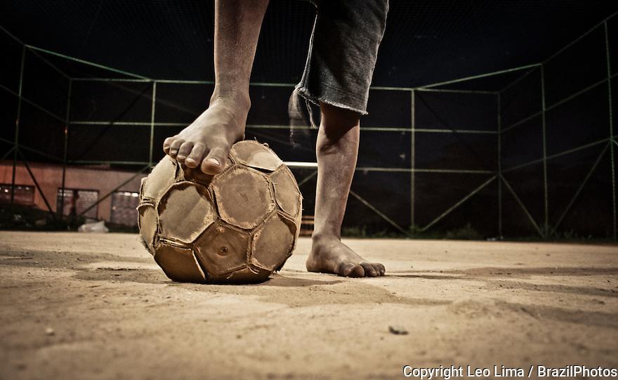 Soccer in Brazil, Poor dark-skinned shoeless boy plays soccer in Favela Fazendinha, a slum belonging to Complexo do Alemao, a group of favelas in northern Rio de Janeiro, Brazil.