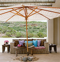 A bamboo sofa dressed with colourful scatter cushions and flanked by a pair of African side tables with a parasol supported by a pile of oval pebbles