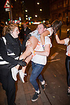 © Joel Goodman - 07973 332324 . 17/11/2013 .  Manchester , UK . A student carries another across the road . Students from Manchester's Universities take part in the annual Carnage pub crawl event at bars in the city's Deansgate Locks venue . Photo credit : Joel Goodman