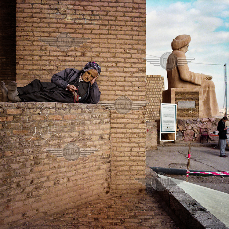 A man with prayer beads reclines against a wall at the South gate of the Citadel of Arbil next to the statue of the poet and historian Mubarak Ben Ahmed Sharaf-Aldin, also known as Abu al-Barakat Ibn al-Mustawfi (1169-1239). The Citadel is an inhabited mound in the centre of the modern Iraqi city of Erbil, which is said to be one of the oldest, continually inhabited places in the world. Earliest traces of habitation on the mound date back to the 5th millennium BC, possibly earlier. The city of Erbil, the fourth biggest in Iraq, is today the capital of Iraqi Kurdistan. .Since 2007 the High Commission for Erbil Citadel Revitalisation (HCECR) has been in charge of the Citadel complex and is carrying out major reconstruction efforts since moving out all remaining residents. It is hoped that 50 families will move back into the Citadel once renovation work and archeological digs have been completed. .