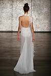 Model walks runway in a one shoulder beaded lace gown with side drape feather trim and floral collar, from Inbal Dror Fall 2018 bridal collection on October 5, 2017; during New York Bridal Fashion Week.