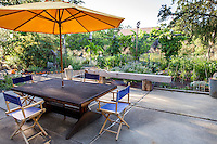 Backyard cement patio with orange umbrella over table with chairs - Barbata meadow garden, Walnut Creek, California