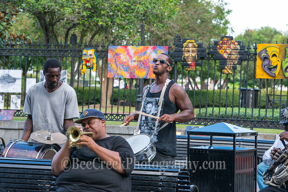 Artist playing their music in Jackson Square in the French Quarter, a popular spot for tourist and locals to come and spend the day. You can see the art hanging on te fence behind them as artist display their art.