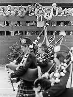 Scottish bagpipes marching band, Festival and Gala Day, the Education Centre, Wester Hailes, Scotland, 1979.  John Walmsley was Photographer in Residence at the Education Centre for three weeks in 1979.  The Education Centre was, at the time, Scotland's largest purpose built community High School open all day every day for all ages from primary to adults.  The town of Wester Hailes, a few miles to the south west of Edinburgh, was built in the early 1970s mostly of blocks of flats and high rises.