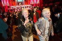 "Jane Abbott Lighty, left, and Pete-e Petersen, from Seattle, walk up the aisle after getting married during an interlude in the Seattle Men's Chorus Holiday Concert in Seattle, Wash., on December 9, 2012. Lighty and Peterson, who have been romantic partners for 35 years received the first same-sex marriage license in Washington state after voter's approved to make it legal. ""I just can't believe this is happening after all these years."" said Peterson. Donald Jenny (left) and Neil Hoyt, from Bellevue, Wash., who have been partners for 23 years all got married during the ceremony.  © Karen Ducey 2012)"