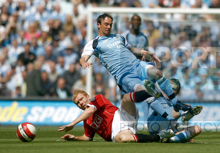 Manchester United's Paul Scholes jumps into a tackle with Manchester City's Stephen Ireland and Michael Johnson