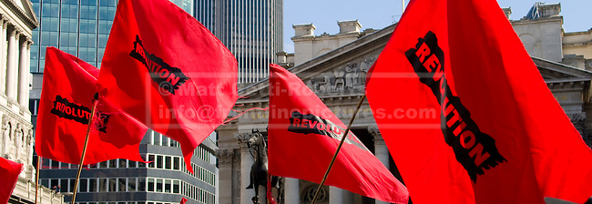 Protesters flags with the word revolution fly outside the Bank of England.