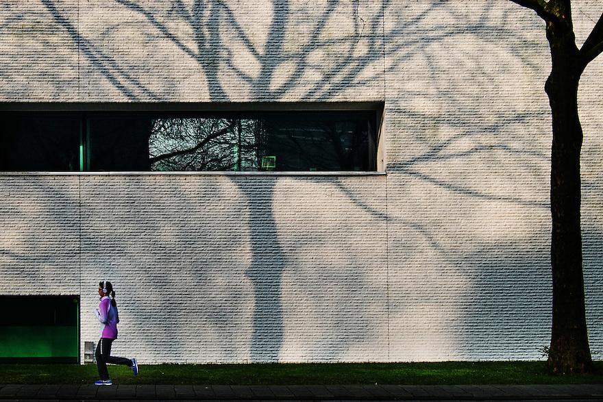 Nederland, Amsterdam, 15 feb 2015<br /> Schaduw van boom op wit gebouw. Een jogger loopt net langs<br /> Foto: (c) Michiel Wijnbergh