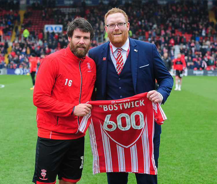 Lincoln City's Michael Bostwick is presented with a shirt by Lincoln City's head of business operations Ian McCallum to mark 600 professional appearances in his career<br /> <br /> Photographer Chris Vaughan/CameraSport<br /> <br /> The EFL Sky Bet League Two - Lincoln City v Grimsby Town - Saturday 19 January 2019 - Sincil Bank - Lincoln<br /> <br /> World Copyright &copy; 2019 CameraSport. All rights reserved. 43 Linden Ave. Countesthorpe. Leicester. England. LE8 5PG - Tel: +44 (0) 116 277 4147 - admin@camerasport.com - www.camerasport.com
