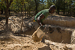Man shoveling sand to build new anti-poaching base, Kafue National Park, Zambia
