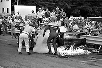 Bobby Rahal (center, in helmet and driving suit) moves through the flames during a pit stop fire to help remove co-driver Geoff Brabham from their Ford Mustang GTP car during the 1983 IMSA race at Road America near Elkhart Lake, Wisconsin.
