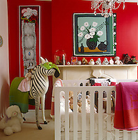 The little girl's toy-filled bedroom is painted a cheerful crimson with a painting by her grandmother, Renee Demsey, displayed above the fireplace