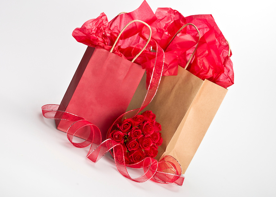 Isolated paper gift bags for saint valentine with rose bouquet