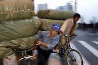 Bicycle porters carrying heavy loads at dusk in Shanghai, China..08 Nov 2004