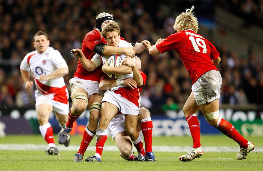 Photo: Richard Lane/Richard Lane Photography. ..England v Wales. RBS Six Nations. 02/02/2008. England's Jonny Wilkinson is tackled by Wales' Ryan Jones.