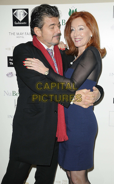 John Altman & guest.The Prince Charming Valentines Ball, Mayfair hotel, Stratton St., London, England..February 14th, 2012.half length black suit red scarf blue dress   arms around waist hug embrace profile .CAP/CAN.©Can Nguyen/Capital Pictures.
