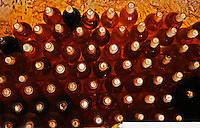 Bottles of sauternes stacked hig, shining golden in the cellar light Chateau de Cerons (Cérons) Sauternes Gironde Aquitaine France