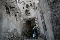 Monday 13 July, 2015: A resident walks through a narrow street in the Old City of Sana'a, a 2,500-year-old cultural heritage site endangered after a fighter jet of the Saudi-led coalition bombed and destroyed a line of residential tower-houses killing 4 residents and reducing to rubble the historial site. The ongoing aerial campaign of bombardments by the Arab states and their western allies led by Saudi Arabia and the heavy fighting against the entrenchment of the Houthi insurgency along the Yemeni main cities from north to south has caused an international alert for the enlisted cultural heritage sites in Yemen, such as the historic town of Zabid, the Old City of Sana'a and the Old Walled City of Shibam. (Photo/Narciso Contreras)