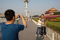 Tian'anmen Square (Place of Heavenly Peace). Tian'anmen Gate. Mao portrait and tourists taking souvenir photos.