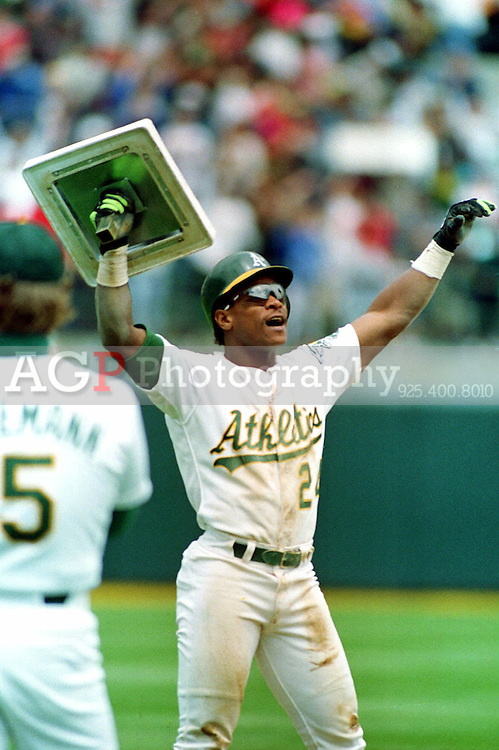 Rickey Henderson of the Oakland Athletics holds up  third base May 1,1991 after breaking Lou Brock's all-time record for stolen bases. The steal was his 939th stolen base it came during the fourth inning of the  A's  game against the New York Yankees in Oakland, Calif.  It was the 12th season of his career. (photo by Alan Greth)