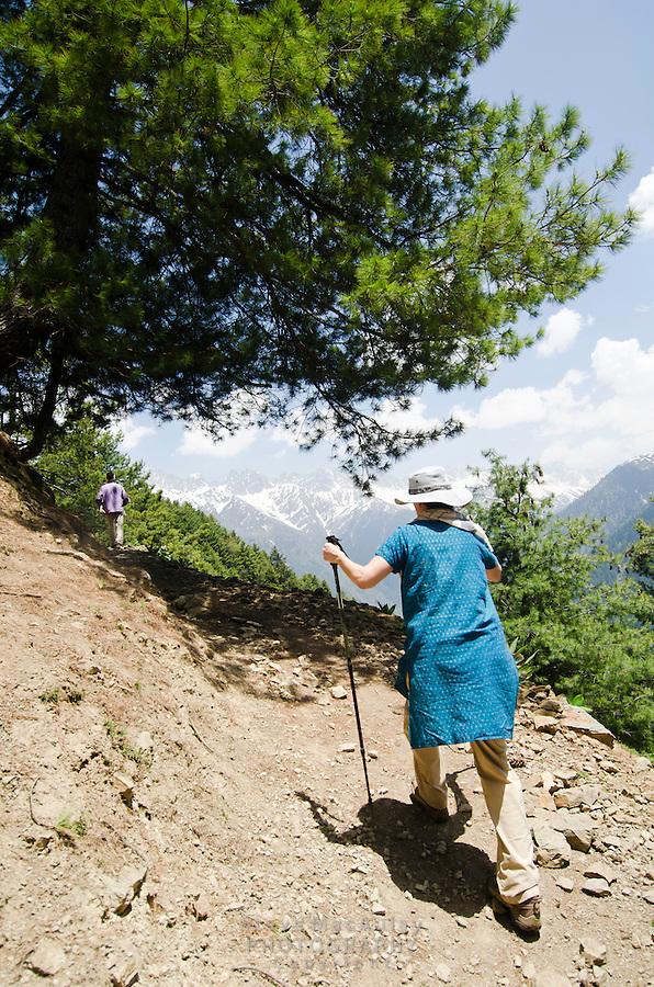 Western tourist climbing up steep trail in the stunning alpine wonderland above Naranag, Kashmir, India.
