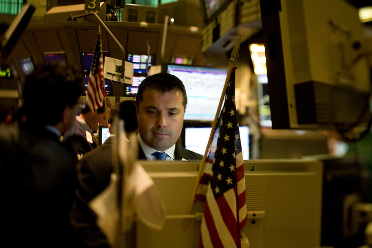©2008 David Burnett / Contact Press Images.Sept 15  2008..Wall St. New York, NY  Financial District..The New York Stock Exchange on Wall St..(giant American Flag and smaller flags on side of building).tourists taking pictures of the Exchange building from the Federal Building (across from Stock Exchange) where George Washington statue is (this is where Washington was first sworn in as President)..Inside Stock Exchange: traders on the floor of the Exchange..outside Lehman Brothers world headquarters in Times Square: guards at the front door, with some employees walking in and out of the building