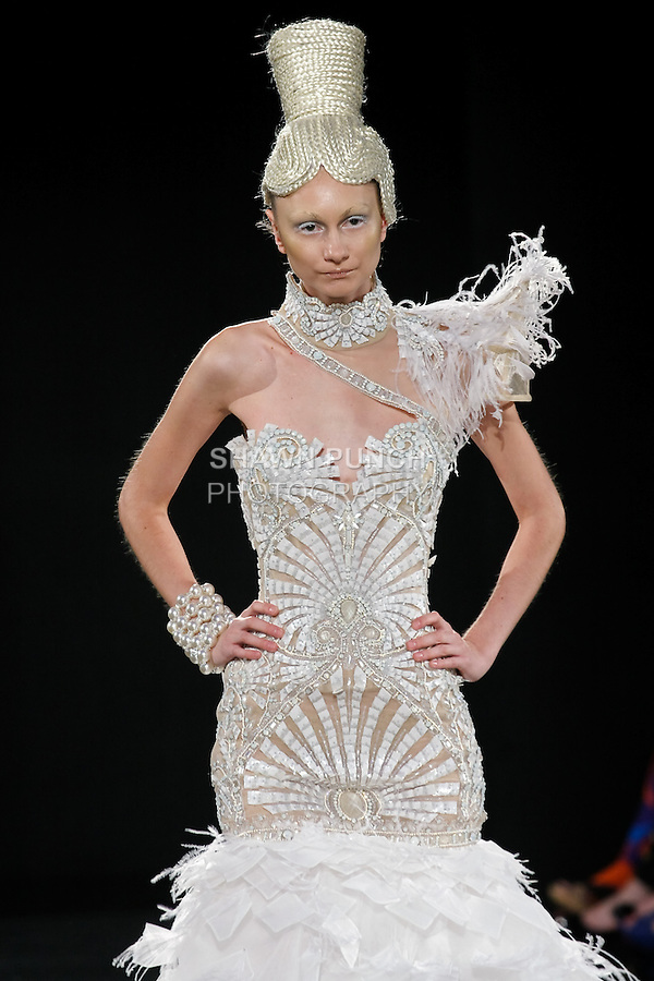Model walks the runway in an outfit by Ezra Santos, for the Ezra Santos Spring 2011 runway fashion show, during Couture Fashion Week, September 11, 2010.