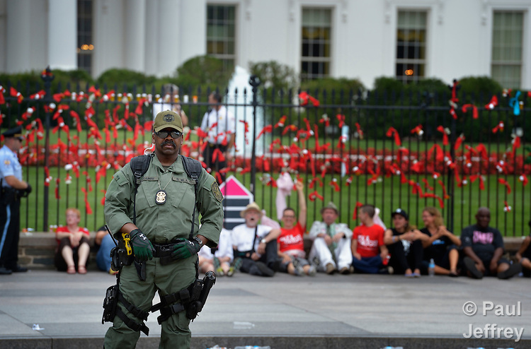 A law enforcement officer observes the crowd as protestors wait to be arrested outside the White House on July 24, 2012. They were criticizing U.S. support for pharmaceutical companies which have resisted generic licenses for their drugs for people living with HIV and AIDS. Several people were arrested after tying red ribbons, many connected to prescription bottles, onto the White House fence. The protest took place during the XIX International AIDS Conference.
