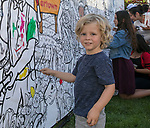 Three-year old Ranger paints on a mural during Artown's Opening Night in Reno on Saturday, July 1, 2017.