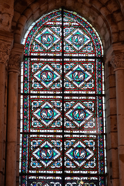 14th century medieval Gothic stained glass window showing  griffons which has beak and wings of an eagle at the body of a lion. By this relationship to the earth and sky it symbolises the two natures of Christ. The Gothic Cathedral Basilica of Saint Denis ( Basilique Saint-Denis ) Paris, France. A UNESCO World Heritage Site.
