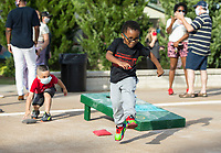 Osafa Hippolyte, 3, of Bentonville dances while playing cornhole Friday, June 19, 2020, during a Juneteenth cookout at Lawrence Plaza in Bentonville. Go to nwaonline.com/200620Daily/ to see more photos.<br /> (NWA Democrat-Gazette/Ben Goff)