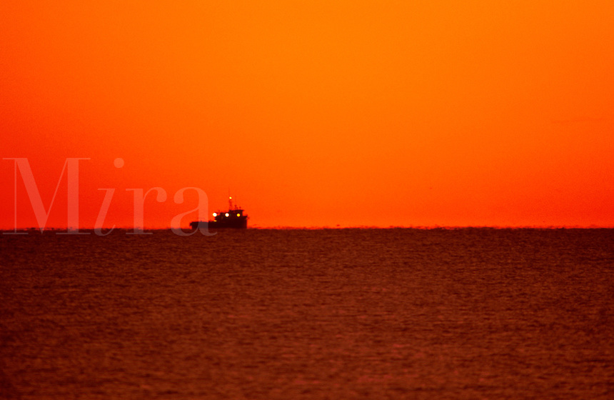 The orange glow of sunrise as it appears over the horizon provides contrast to the silhouette of an offshore supply ship and the dark water.