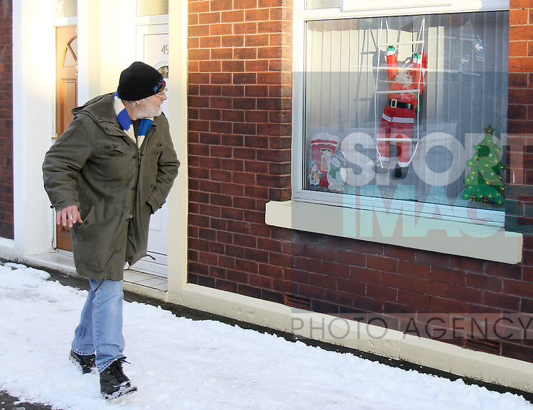 A Blackburn fan stares at a Father Christmas in the window on his way to the stadium