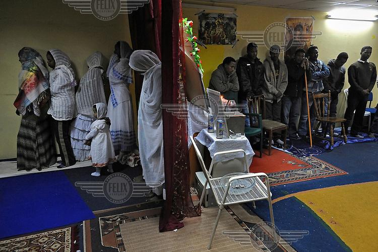 Eritrean asylum seekers conduct a prayer at their makeshift church.