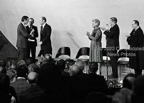George H.W. Bush, new Director, Central Intelligence Agency (CIA), is congratulated by former CIA Director William Colby after making remarks following his taking his oath of office as United States President Gerald R. Ford looks on at the agency's headquarters in Langley, Virginia on January 30, 1976. At right, Barbara Bush, Vernon Walters, Deputy Director of the CIA, and U.S. Supreme Court Associate Justice Potter Stewart applaud.<br /> Credit: Barry Soorenko / CNP