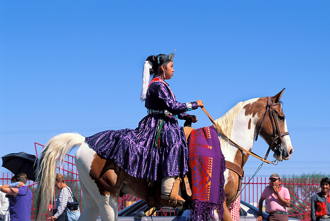 A Navajo girl dressed in a traditional dress rides her horse during a parade in Gallup NM