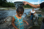 November 07, 2014. &quot;Water it&acute;s the real thing&quot;<br /> Edwin Salguero washes her daughter Nemia in Acelhuate river (Nejapa, El Salvador) because they don&rsquo; t have drinking water at home. The river is contaminated. Edwin and his family have to walk near two hours to get the river. <br /> The people of Nejapa in El Salvador, have no drinking water because the Coca -Cola company overexploited the aquifer in the area, the most important source of water in this Central American country. This means that the population has to walk for hours to get water from wells and rivers. The problem is that these rivers and wells are contaminated by discharges that makes Coca- Cola and other factories that are installed in the area. The problem can increase: Coca Cola company has expansion plans, something that communities and NGOs want to stop. To make a liter of Coca Cola are needed 2,4 liters of water. &copy;Calamar2/ Pedro ARMESTRE