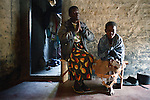 MPHANDULA, MALAWI - AUGUST 21: Ethel Dailesi, age 44, prays with her daughter Rebecca Masawo, age 10, in her living-room after taking her drugs on August 21, 2006 in Mphandula village, about 30 miles outside Lilongwe, Malawi. Ethel was diagnosed with HIV/Aids in 2004 and has been on antiretroviral drugs since December 2005. She has just taken her medicine. She is often sick and her two daughters take care of her. Her children cook and clean for her. The girls attend a school nearby but they usually stay home when their mother is too sick. Mphandula is a poor village in Malawi, without electricity or clean water. Nobody owns a car or a mobile phone. Most people live on farming. About 7000 people reside in the village and the chief estimates that there are about five-hundred orphans. Many have been affected by HIV/Aids and many of the children are orphaned. A foundation started by Madonna has decided to build an orphan center in the village through Consol Homes, a Malawi based organization. Raising Malawi is investing about 3 million dollars in the project and Madonna is scheduled to visit the village in October 2006. Malawi is a small landlocked country in Southern Africa without any natural resources. Many people are affected by the Aids epidemic. Malawi is one of the poorest countries in the world and has about 1 million orphaned children. (Photo by Per-Anders Pettersson)