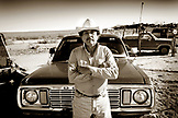 MEXICO, Baja, Magdalena Bay, Pacific Ocean, a young local man standing in front of his truck on Isla Magdalena