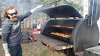 NWA Democrat-Gazette/FLIP PUTTHOFF <br /> Corey Milford with the Ozark Off-Road Cyclists smokes ribs and chicken   April 6 2019    for festival goers.