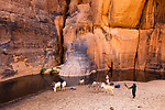 Chad (Tchad), North Africa, Sahara, Ennedi, young women filling up canisters with water in a canyon