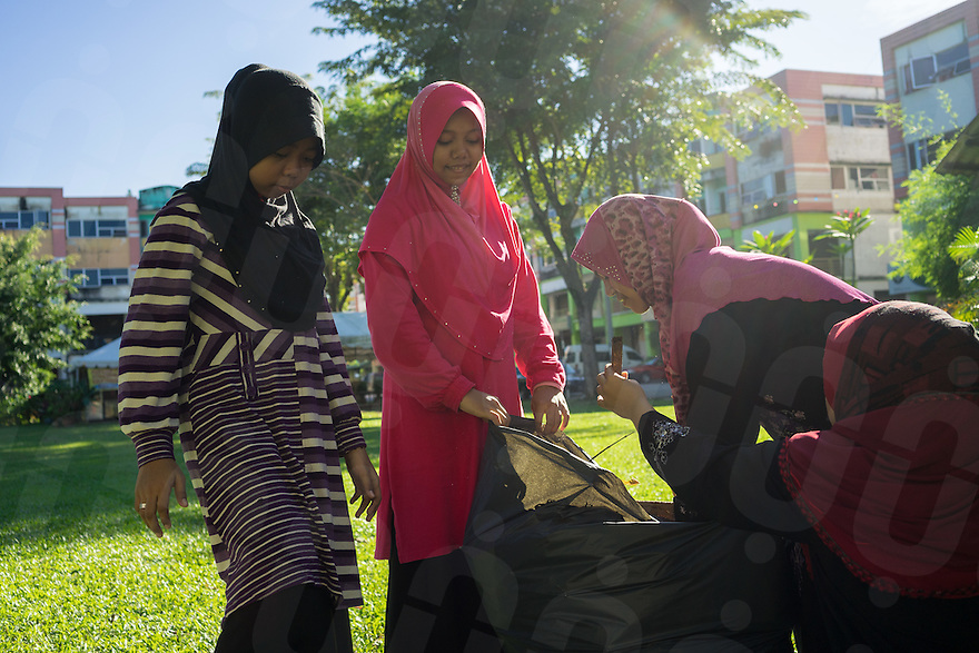 """January 10, 2015 - Rawang (Malaysia). Young members of the organisation cleans the park of the """"Global Ikhwan village"""", a compound of commercial and residential estates owned by the organization in Rawang, a small town in the north of Kuala Lumpur. The enterprise, which employs 4,000 people worldwide through its complicated network of subsidiaries,operates restaurants, clothing shops, noodle factories and health clinics in Malaysia, Indonesia, Thailand, Middle East and Australia. © Thomas Cristofoletti / Ruom"""