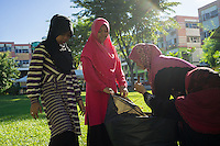 "January 10, 2015 - Rawang (Malaysia). Young members of the organisation cleans the park of the ""Global Ikhwan village"", a compound of commercial and residential estates owned by the organization in Rawang, a small town in the north of Kuala Lumpur. The enterprise, which employs 4,000 people worldwide through its complicated network of subsidiaries, operates restaurants, clothing shops, noodle factories and health clinics in Malaysia, Indonesia, Thailand, Middle East and Australia. © Thomas Cristofoletti / Ruom"