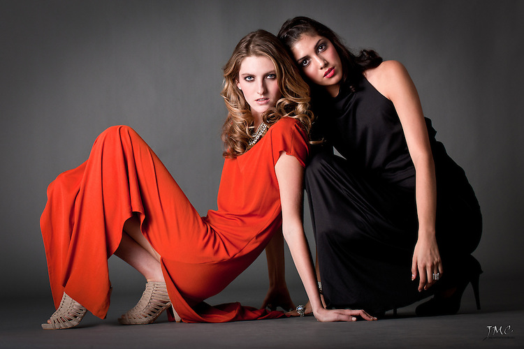 Two beautiful young fashion models posing together in orange and black dresses